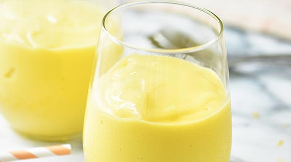 This easy mango smoothie has 5 ingredients and only takes 5 minutes to put together! showmetheyummy.com #mango #smoothie #glutenfree #vegetarian #lemon #breakfast #drinks #greekyogurt