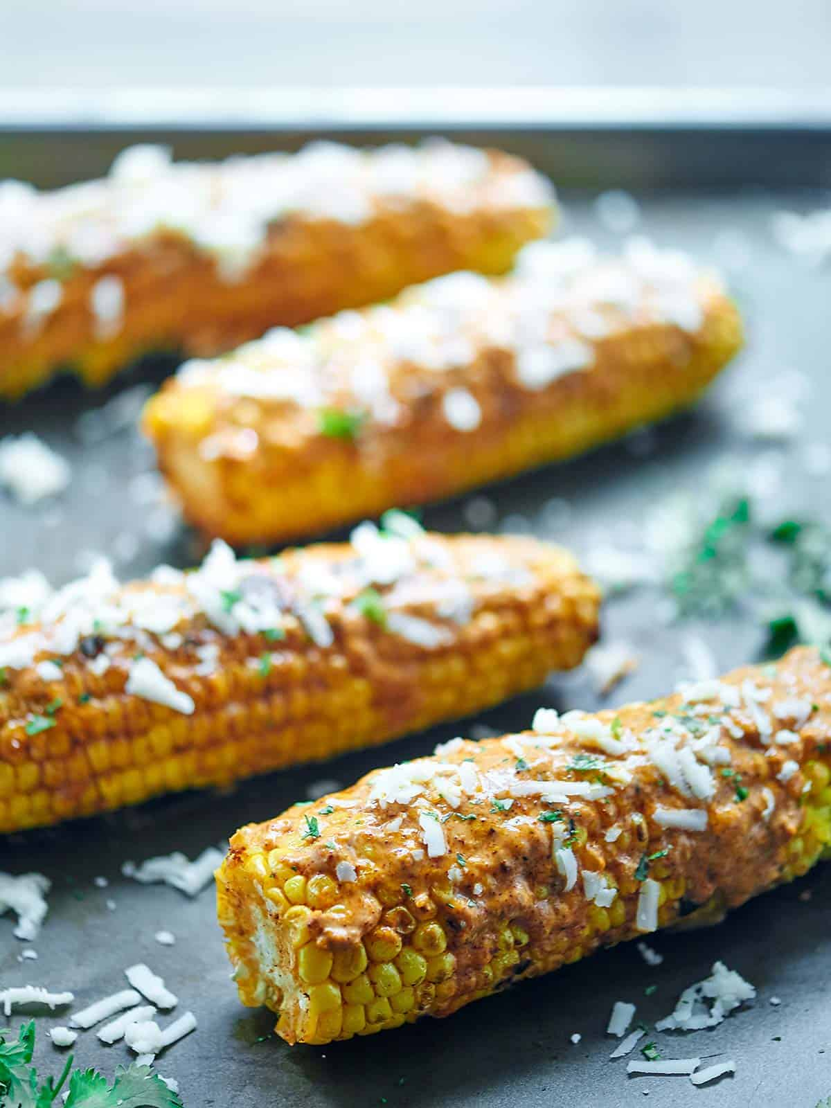Mexican Grilled Corn. Grilled corn that's smothered in a creamy, smoky butter and topped with salty Mexican cheese - cotija - and fresh cilantro! showmetheyummy.com #grilling #corn #mexican #cheese #butter