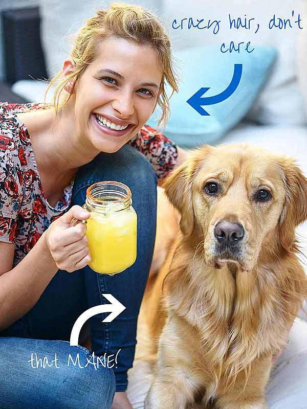 Woman holding margarita next to dog