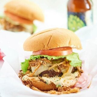 Pepper Jack Stuffed Burger with Jalapeno Cream Sauce. A juicy burger filled with gooey cheese and topped w/ a creamy jalapeno sauce and crispy fried onions! showmetheyummy.com #burger #spicy #cheese #fried #grilling