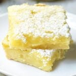 Summer Shandy Lemon Bars! The base is a simple shortbread crust. It's rich, buttery, and perfectly sweet. The filling is a twist on a classic. It's light, lemony, and the Summer Shandy comes through beautifully. showmetheyummy.com #summer #shandy #beer #lemon #lemonbars #dessert #shortbread #summershandy