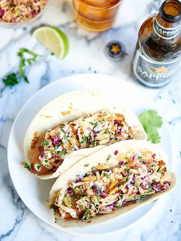 Beer Battered Fish Tacos w/ Asian Slaw. Flour tortillas stuffed with crispy, golden, tender, beer battered cod and topped with toasty, crunchy, fresh coleslaw! showmetheyummy.com #seafood #tacos