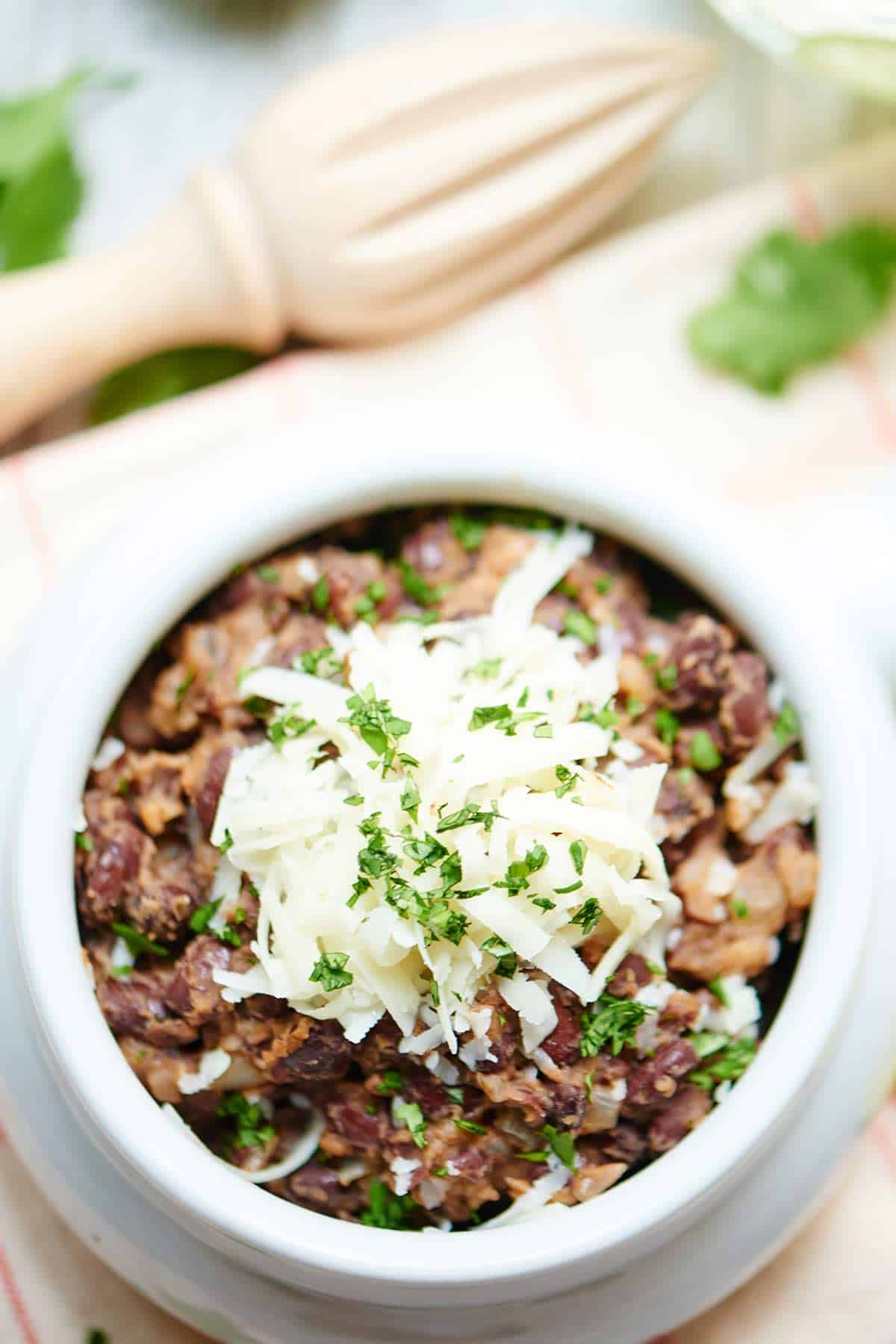 Bowl of easy black beans with cheese above