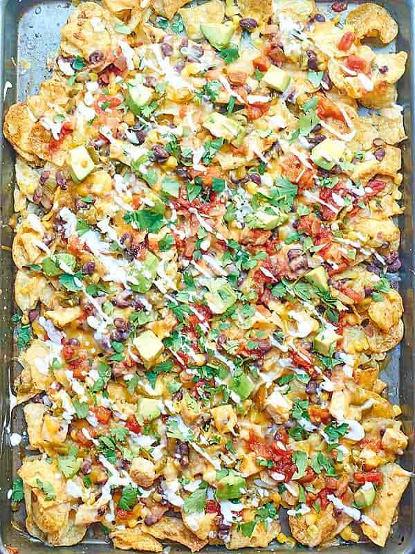 Kettle Chip Chicken Nachos. Jalapeno and Sea Salt Kettle Chips are piled with black beans, chicken, gooey cheese, sweet corn, dollops of sour cream, and some green chiles and jalapeños! showmetheyummy.com #nachos #chicken
