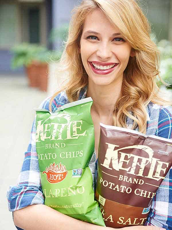 woman holding two bags of kettle chips