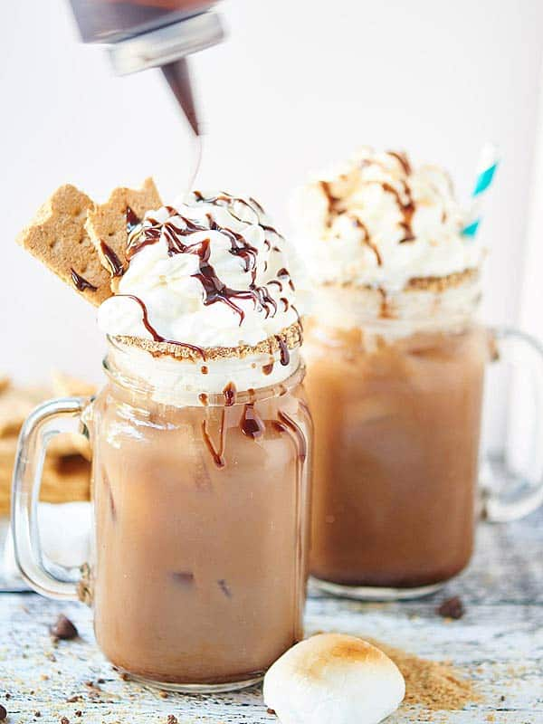 two jars of smores iced coffee with whipped cream and chocolate drizzle
