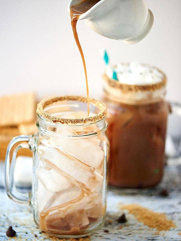 Iced coffee being poured into jar of ice