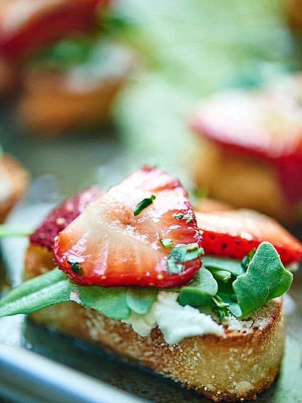 This Strawberry Goat Cheese Bruschetta is my new favorite appetizer. Slightly chewy bruschetta is topped with creamy goat cheese, peppery arugula, juicy strawberries, and earthy basil. showmetheyummy.com #bruschetta #vegetarian