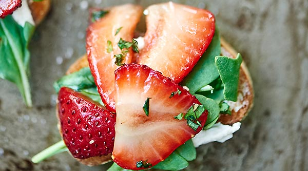 This Strawberry Goat Cheese Bruschetta is my new favorite appetizer. Slightly chewy bruschetta is topped with creamy goat cheese, peppery arugula, juicy strawberries, and earthy basil. showmetheyummy.com #bruschetta #vegetarian
