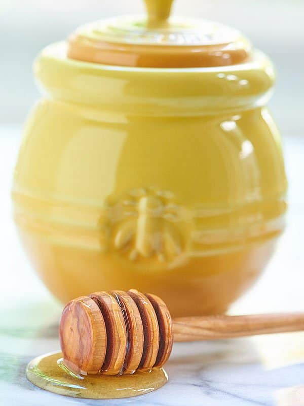 honey dipper next to yellow container