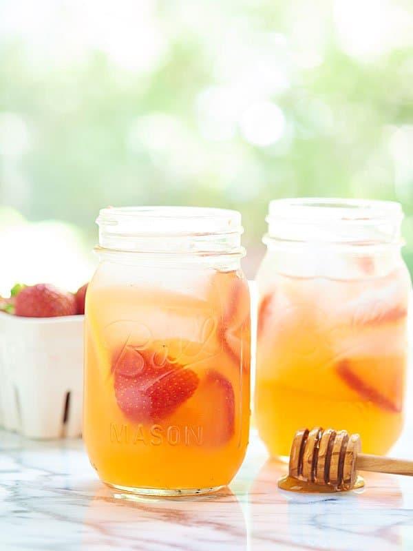two mason jars of honey strawberry lemonade from the side