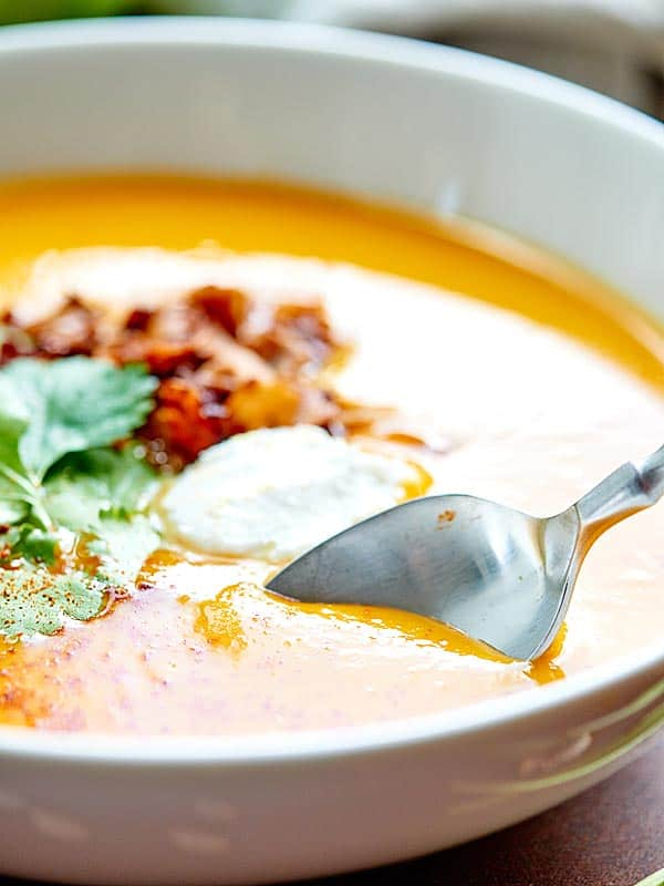 This Crockpot Butternut Squash Soup Recipe is vegan, gluten free, healthy, full of vegetables, and topped with coconut cream, cilantro, and coconut bacon! showmetheyummy.com #vegan #soup