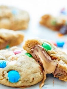 These Peanut Butter Salted Caramel Cookies are made of a simple peanut butter dough, studded with M&Ms, white chocolate chips, and salty pretzels. To make these even more decadent, they get stuffed with rolos! showmetheyummy.com #dessert #cookies