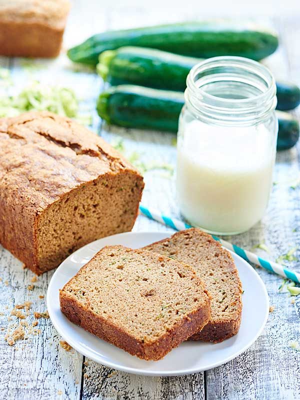 two slices of zucchini bread on plate next to loaf and mason jar of milk