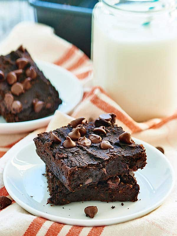 Two brownies stacked on a plate with milk and another brownie in the background