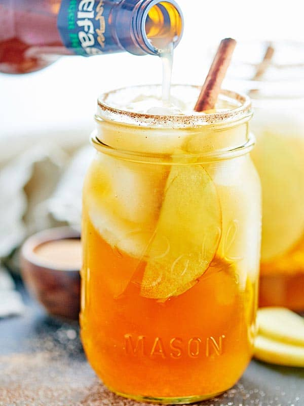 This Fall Sangria is so easy & is filled with maple syrup, cinnamon, orange, vanilla, rum, apples, pear, & pinot grigio! Don't forget the cinnamon sugar rim! showmetheyummy.com #sangria #rum