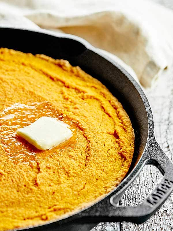 This pumpkin cornbread is a great, easy, vegan side dish for any meal! It's made with whole wheat pastry flour, coconut oil, and smothered in maple syrup! showmetheyummy.com #vegan #pumpkin