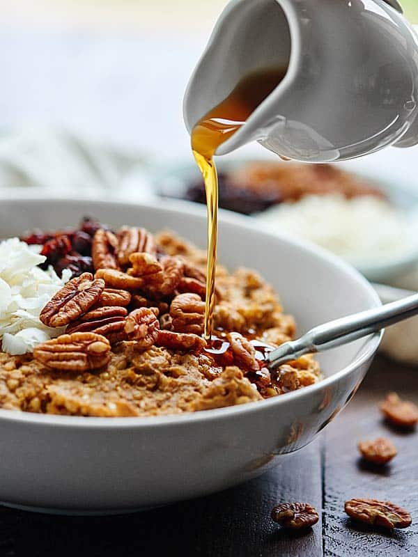 crockpot pumpkin oatmeal in bowl being drizzled with maple syrup