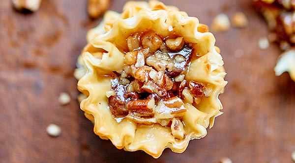 These pecan pie bites are cute, bite sized, quick & easy to make, & filled w/ a maple bourbon caramel. Chocolate chips are optional, but highly recommended! showmetheyummy.com #thanksgiving #pecanpie