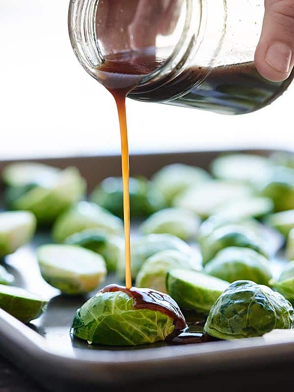 balsamic vinegar being drizzled over baking sheet of brussels sprouts