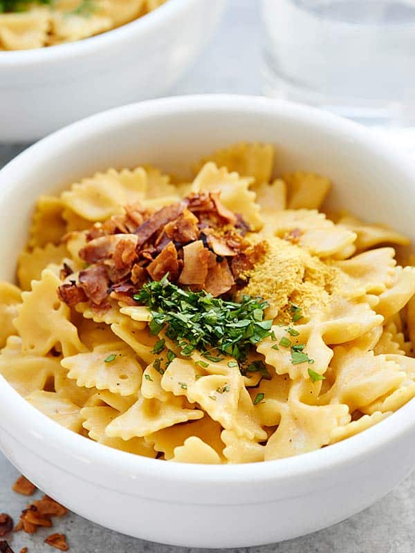 bowl of mac and cheese with coconut bacon and cilantro