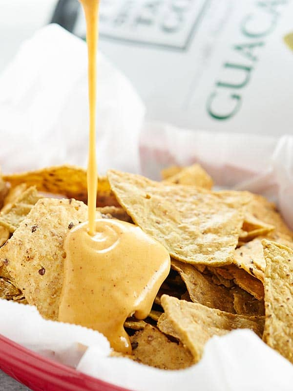 queso being drizzled over basket of tortilla chips