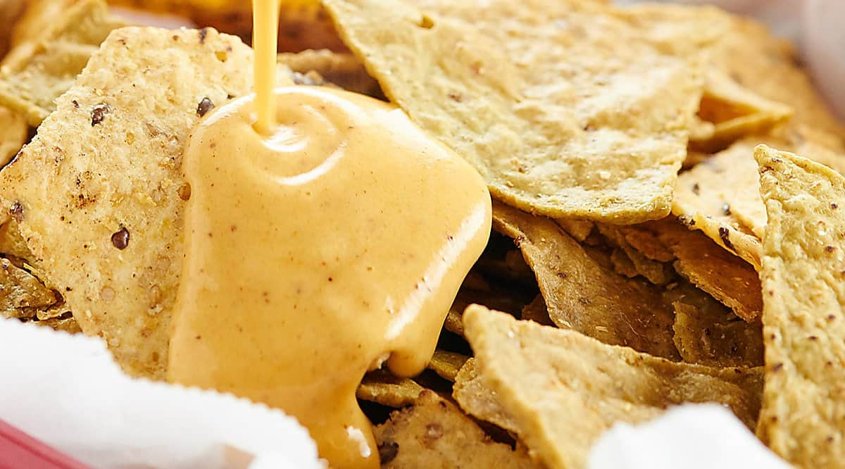 Queso dip drizzled over chips
