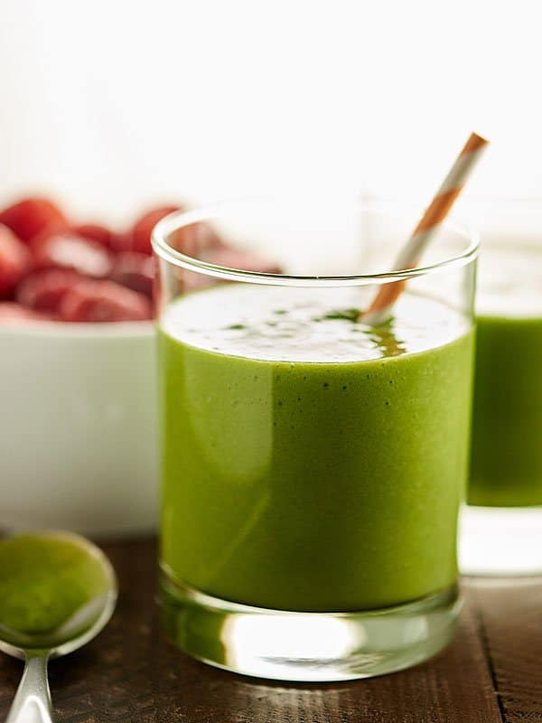 Tropical green smoothie in cup with straw side