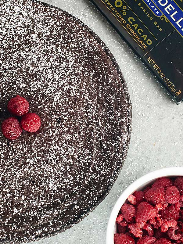 This Vegan Flourless Chocolate Cake Recipe is easy to make, gluten free, & is made w/ better for you ingredients to make a slightly healthier, fudge-y cake! showmetheyummy.com #vegan #flourlesschocolatecake
