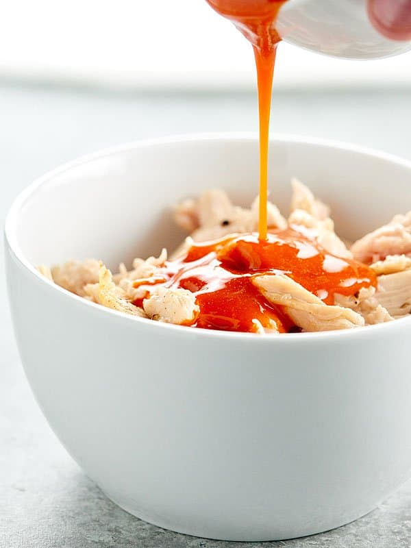 bbq sauce being poured over bowl of shredded chicken