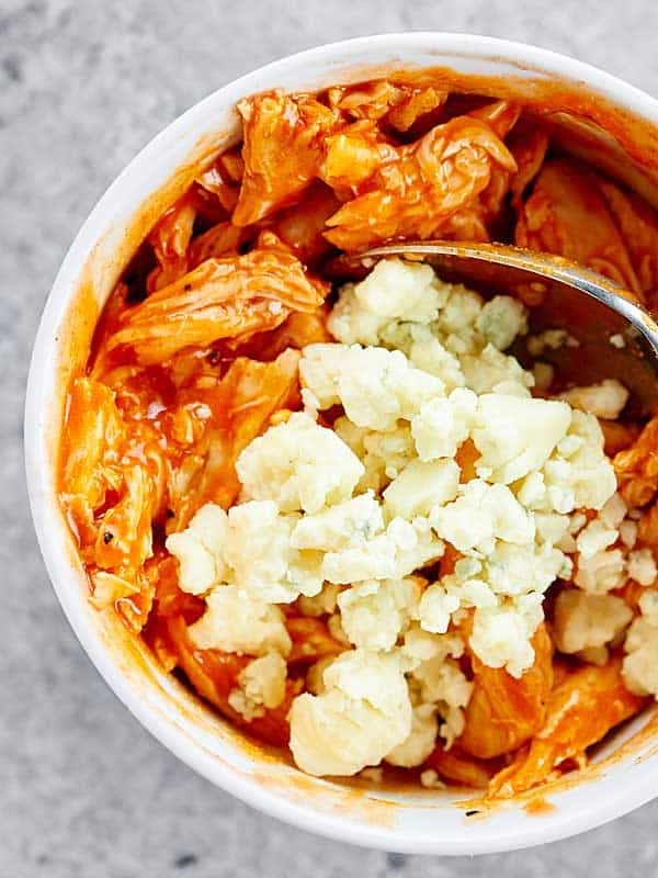 bbq sauce covered chicken with cheese in bowl above