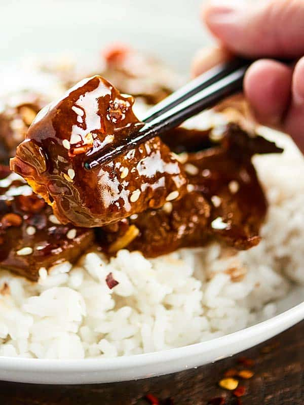 Piece of Mongolian beef being picked up off plate with chopsticks