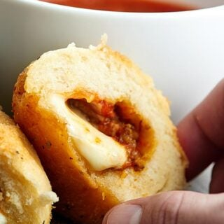 Pre made biscuits are stuffed w/ pizza sauce, cheese, sausage/pepperoni & smothered in butter & pizza spices to make this gooey Stuffed Pizza Rolls Recipe! showmetheyummy.com #pizzarolls #sausagepizza