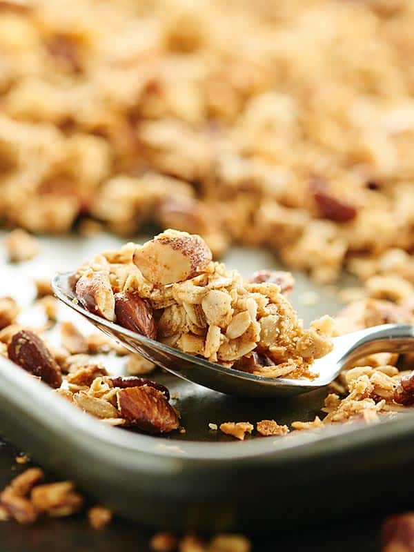 Vegan granola on baking sheet with spoon