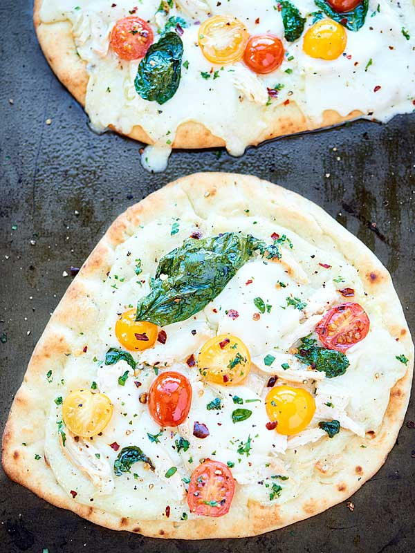 This Chicken Naan Pizza is ready in 20 minutes or less! Garlic naan is topped with a healthy alfredo sauce, diced chicken, mozzarella, tomatoes and basil! showmetheyummy.com #pizza #chickenalfredo