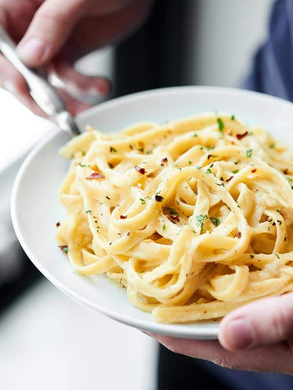 This Healthy Alfredo Sauce is a lightened up version of a classic (530 calories for the ENTIRE recipe). Made with greek yogurt, skim milk, and parmesan! showmetheyummy.com #healthy #alfredosauce