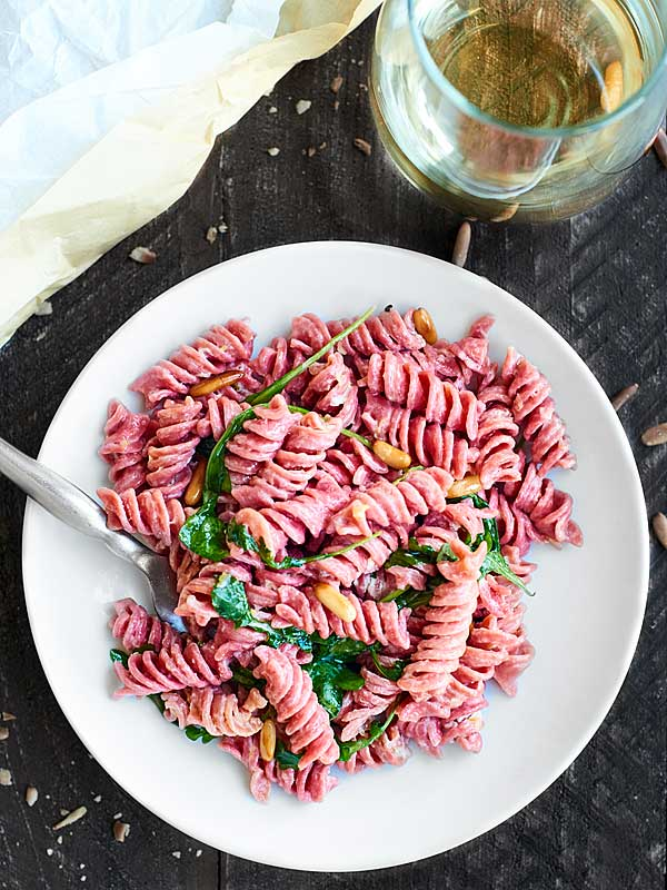 plate of beet pasta next to glass of white wine above