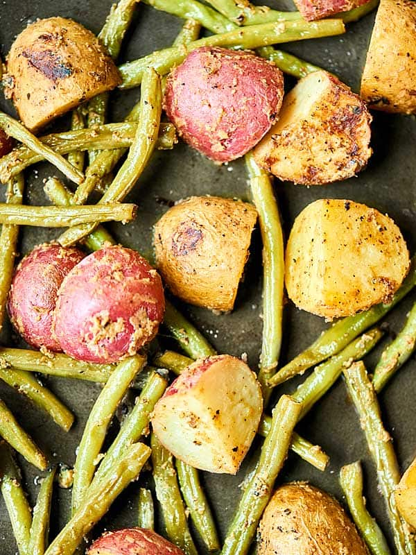 Potatoes and green beans on baking sheet above