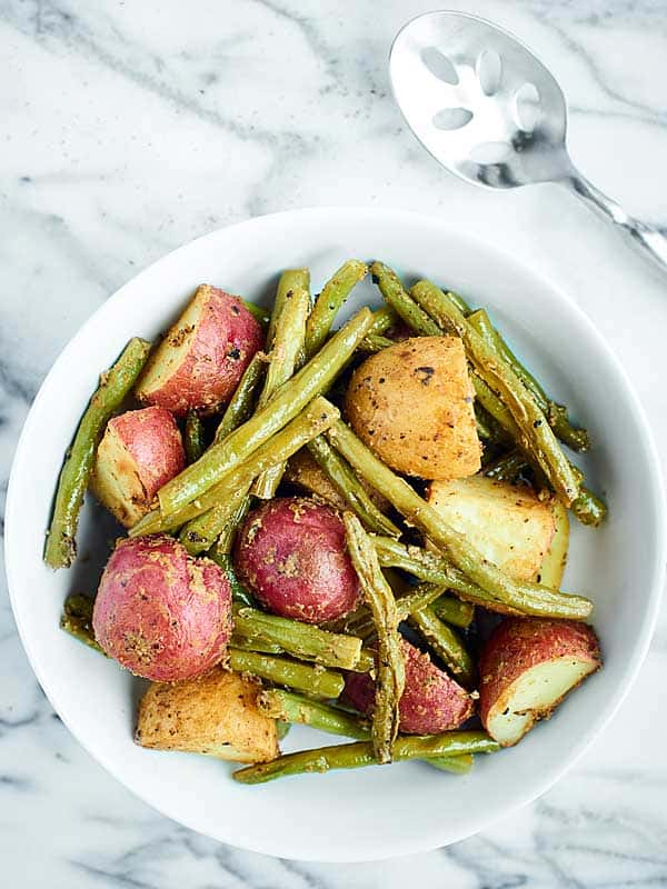 Roasted potatoes and green beans on a plate above