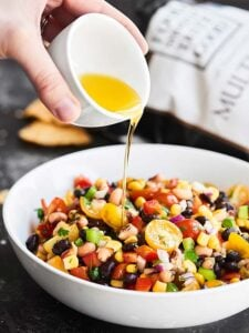 Texas caviar in a bowl with dressing being drizzled over it