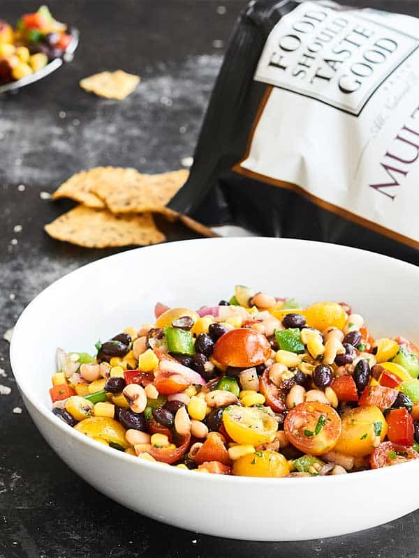Ready for the easiest Cinco de Mayo recipe? This Texas Caviar comes together in a matter of minutes and is full of fresh veggies - peppers, onion, tomatoes - beans, corn, and a tangy dressing! showmetheyummy.com #texascaviar @fstgchips #foodshouldtastegood #ad