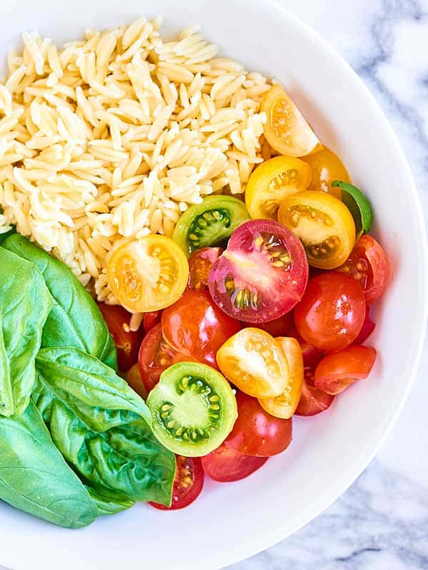 This Caprese Pasta Salad is so quick and easy to put together! Full of orzo pasta, mozzarella, sun dried tomatoes, fresh basil, tangy balsamic, and salty parmesan! showmetheyummy.com #pastasalad #caprese