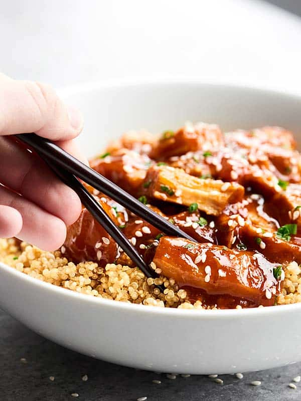 Piece of chicken being picked up out of bowl with chopsticks