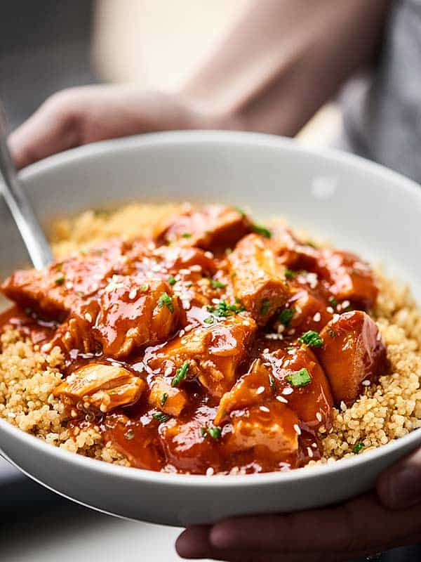 Honey sriracha chicken over quinoa in a bowl held