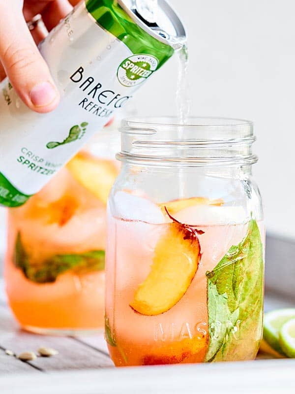 A refreshing adult's only cocktail, this Peach Lemonade Spritzer is made with fresh peaches, tart lemons, earthy basil, vodka, and a crisp white wine spritzer! showmetheyummy.com Recipe made in partnership with @BarefootWine #ad #cocktail