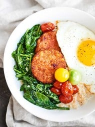 Creamy parmesan oats are topped with garlicky greens, crispy hash browns, fresh tomatoes, and a runny egg to make this the BEST Vegetarian Breakfast Bowl Recipe. showmetheyummy.com #ad #breakfastbowl @drpraegers