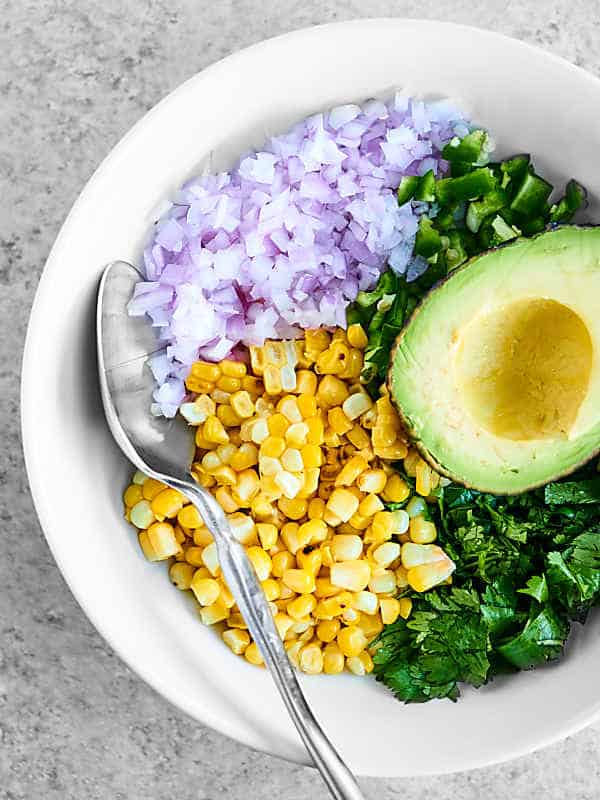 bowl of avocado, corn, onions, and cilantro