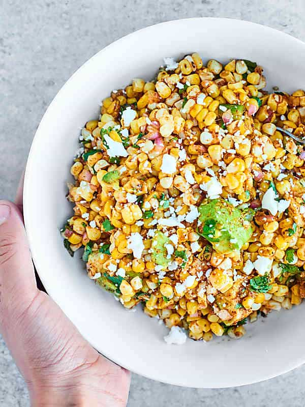 This Mexican Corn Salad will totally be the star of your next BBQ. Full of roasted corn, creamy avocado, fresh cilantro, lime, and tons of spices, it's SO full of texture and flavor. showmetheyummy.com #cornsalad #mexicancornsalad