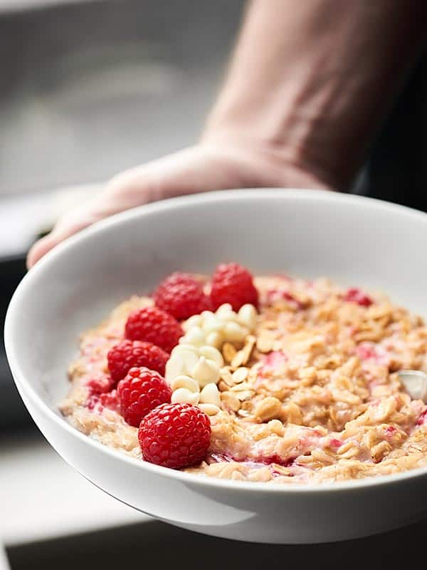 bowl of white chocolate berry cheesecake oatmeal held