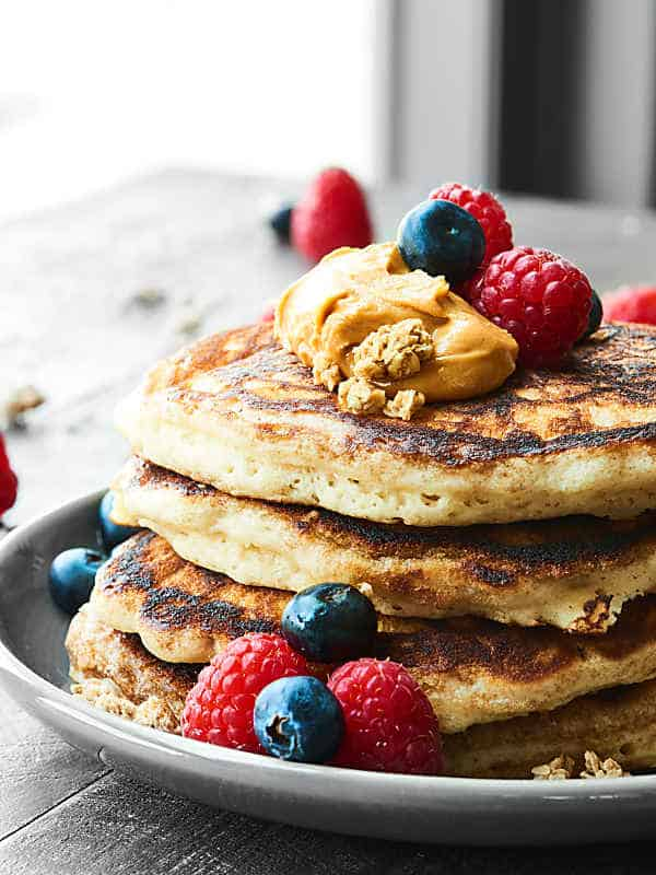 stack of buttermilk pancakes with peanut butter and berries